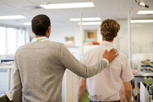 Businessman Comforting Colleague In Office