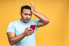 Portrait Of African American Indian Black Man, Shocked, Surprised, Wide Open Mouth, Mad By What He Sees On His Cell Phone, Isolated On Yellow Background. Negative Human Emotions, Facial Expressions.