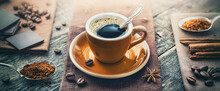 A Cup Of Aromatic Black Coffee, A Coffee Maker, Coffee Beans Of Different Varieties On The Table. Morning Espresso Or Americano Coffee For Breakfast In A Beautiful Brown Cup.
