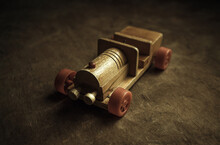 An Old Wooden Car With Red Wheels On A Wooden Table. A Children's Toy In A Retro Style.