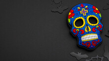Halloween Backgrounds, Mexican Culture And Dia De Los Muertos (day Of The Dead) Concept With Colorful Skull And Black Confetti Isolated On Dark Background With Copy Space