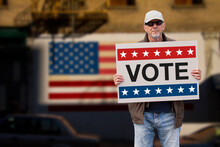 Man With Cap, Blue Jeans And Sunglasses Holding A Cardboard Sign Text VOTE With American Stars And Stripes Flag On A Wall In The Background. American Patriotic Background For Election Day.