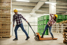 Funny Moments On A Break At Work, A Back To Childhood. Happy Couple Behaves Unprofessionally In The Storage With Stock Of Products. Driving On A Hand Truck And Losing Balance. Yellow Protective Helmet