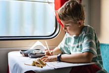 Focused Male Kid Drawing Writing Paper Notes Enjoying Travel By Train At Luxury Railway Carriage