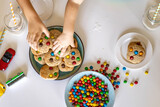 Funny male brothers eat cookies with round multi-colored sweets m&m and drink milk. Top view.