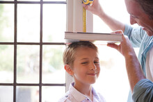 Father Measuring Son's Height On Door