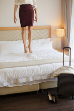 Businesswoman Jumping On Bed In Hotel Room