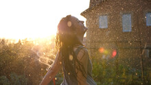 Joyful Brunette Girl Enjoys Her Evening In The Countryside By Dancing In The Rain. Stunning Golden Sun Rays Shine On Playful Young Woman Spinning And Enjoying A Spring Shower. CLOSE UP, LENS FLARE