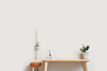 Wooden TV Stand With Houseplants And Chair Near Light Wall