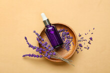 Bowl With Bottle Of Lavender Essential Oil And Flowers On Color Background