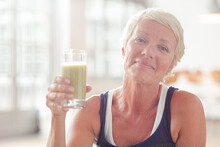 Older Woman Drinking Juice On Exercise Mat
