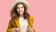 Smiling Young Woman Wearing Stylish Coat, Hat On Pink Studio Background With Copyspace. Portrait Of Happy Joyful Girl Looking Aside With Long Hair Flying In The Wind. Style Fashion And Casual Garment