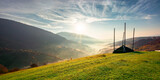 Fototapeta Kawa jest smaczna - rural landscape at sunrise. beautiful autumnal mountain scenery. green grassy meadow on the hillside. fog down in the valley. sun and fluffy clouds above horizon