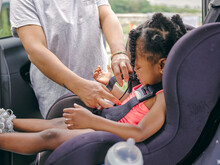 Woman Fastening Daughters Seat Belt In Car