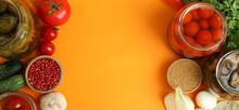 Jars Of Pickled Vegetables And Ingredients On Orange Background