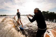One-armed Man Riding On Wakeboard And Instructor Explains How To Do It Right