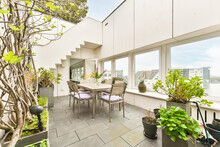 Terrace With Table And Green Potted Plants