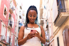 Black Woman Using Smartphone In Narrow Street In Old City