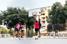 Company Of Diverse Friends Playing Basketball On Sports Ground