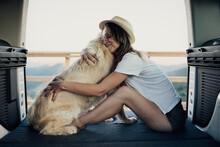 Female Owner Embracing Dog In Camper