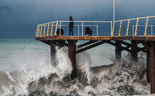 Waves Of A Stormy Sea Crushing On Pier, Fishermen With Fishing Rods On The Pier Against The Dark Sky