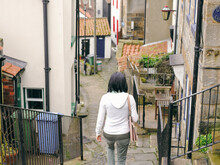 UK, Rear View Of Woman Descending Steps In Old Town