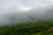 Landscape View Of Alps. Peaks Cover By Clouds And Fog Because Of Stormy Weather.