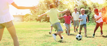 Group Of Happy Kids Are Running And Playing Football In Park At Summer Day