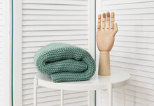 Knitted Plaid And Wooden Hand On Table Near Light Wall