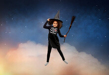 Halloween, Holiday And Childhood Concept - Smiling African American Girl In Black Costume Dress And Witch Hat With Broom Over Starry Night Sky And Cloud Background
