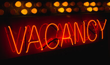 """Red Neon Sign With The Word """"vacancy"""" With Light Bulbs Across The Top"""