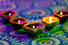 Lit Candles In Small Decorative Clay Pots Burning On Patterned Table Cloth