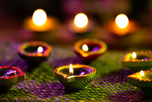 Lit Candles In Small Decorative Clay Pots Burning On Woven Table Cloth