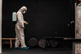 In the preventively isolated gym, a person in a special protective suit refreshes and cleans the air and space with a nozzle. COVID19 prevention, coronavirus situation, locking down