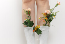 A Beautiful Image On A White Background With Long Slender Legs In White Stockings And Autumn Flowers And Fashionable Sports Leather Sneakers, Perfect For A Store Catalog. Flowers In Socks.