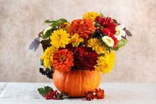 A Beautiful Autumn Bouquet Of Yellow And Red Flowers In A Pumpkin. The Concept Of Autumn, Thanksgiving Day. Copy Space.