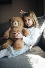 Happy Little Girl Hugging A Teddy Bear At Home.