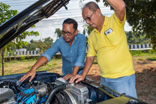 Two Men Looking Under The Hood Of American Muscle Car In Thailand