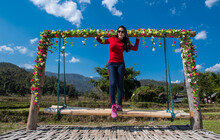 Thai Woman Standing On Swing On A Bamboo Patio In North Thailand
