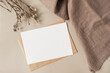 Leinwandbild Motiv Blank paper sheet card with mockup copy space and dry floral branch and blanket cloth on neutral beige background. Minimal aesthetic wedding invitation template. Flat lay, top view
