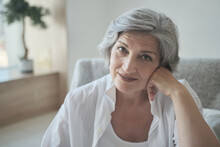 Cheerful Successful Grey Haired Senior Retired Grandma Enjoying Comfortable Posing In Cozy Room, Happy Attractive Senior Adult Female Woman Looking At Camera Sitting Alone On Sofa At Home