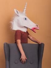 Unrecognizable Child In Unicorn Mask Against Armchair