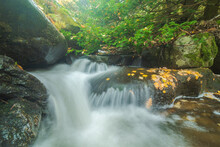 Fast Waterfall Between Boulders And Autumn Trees