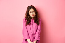 Cute Coy Girl Making Silly Face, Wants Something, Begging For Gift, Standing Against Pink Background