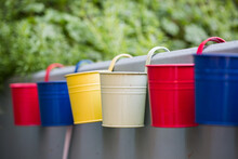 Selective Of Colorful Buckets Hanging From A Wall Of A Balcony