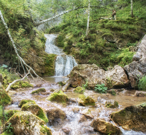 Beautiful view of a flowing rocky waterfall surrounded by greens and trees in the woods