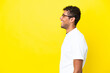 Young handsome Brazilian man isolated on yellow background laughing in lateral position