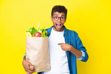 Young Brazilian Man Holding A Grocery Shopping Bag Isolated On Yellow Background With Surprise Facial Expression