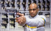 Portrait Of Confident Latino Choosing Handgun In Armory Shop, Testing Pistol Aiming