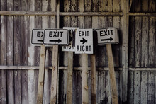 Exit Signs Against Old Wooden Structure